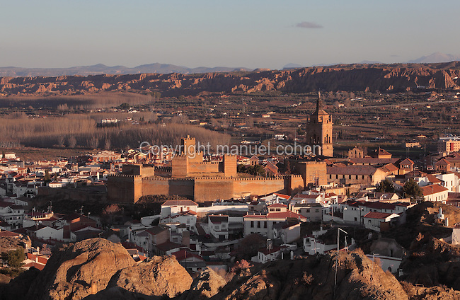 View of the town of Guadix, with the Alcazaba, the 11th century Moorish castle, declared a National Artistic Monument in 1931, and the cathedral, the Catedral de la Encarnacion de Guadix, built 16th - 18th centuries in Baroque style, Guadix, Andalusia, Southern Spain. Half the population of Guadix live in troglodyte dwellings, underground cave homes built to keep out the heat of the summer and the cold of the winter. Picture by Manuel Cohen