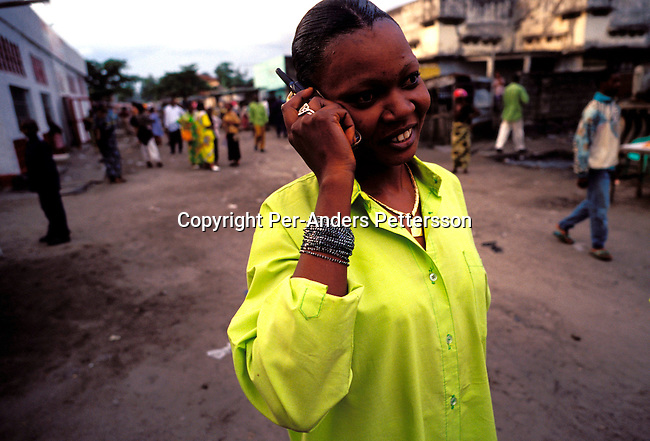 dicocon00209.Congo. Kinshasa. Technology Communications, cell phone. An unidentified young woman talking on a mobile phone after a church service on February 28, 2002 in Lingwala district in Kinshasa, Congo. Mobile phone has been available since 1999 has made a tremendous difference in a country like the Congo. The mobile phone is the ultimate status thing in Congo and people can be seen clinging their cell phones looking important. There are four competing providers and people can now reach friends and relatives in some of the cities in Congo or make appointments and business meeting in Kinshasa. The local telephone system is non-existent. A phone costs around $100 and local phone calls are about 35 cents US, and international calls about $ 1 per minute, a bargain compared to earlier about $ 10 per minute for overseas calls from a local phone..©Per-Anders Pettersson/iAfrika Photos