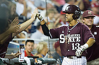 Mississippi State second baseman Brett Pirtle (13) is greeted by his teammates after he scored against the Indiana Hoosiers during Game 6 of the 2013 Men's College World Series on June 17, 2013 at TD Ameritrade Park in Omaha, Nebraska. The Bulldogs defeated Hoosiers 5-4. (Andrew Woolley/Four Seam Images)