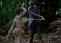 Potolico Whipping Pygmy Boy.The whipping is more severe on the last day and includes a ceremony where the boys are secluded within a phalanx of men all carrying whips... the men are met halfway thru the village with women carrying whips and a melee ensues trying to control the destiny of the child... the men win... the boy is now a man and cannot be claimed as a child anymore by his mother.  There is also ritual scarification on this day and each boy is paraded, one by one thru the village accompanied by a masked elder and someone to collect the money being thrown at his dancing feet....