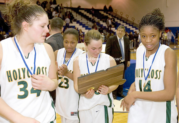 NEW BRITAIN, CT--10 MARCH 2007--031007JS17- Holy Cross' Kelly McKeon, reads the CIAC Championship plaque as teammates Chelsea Cracco, Morgan Johnson and Kim Clements celebrates their 67-58 win over Career Magnet to take the Class M state finals Saturday at Central Connecticut State University in New Britain. <br /> Jim Shannon / Republican-American