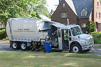 Waste collection workers pick up a black waste cart on a suburban street using an automated truck, which is part of the Automated Waste Collection Service launched in 2011 in Cleveland, Ohio, USA.  Recyclables are collected from the blue carts in the same way.