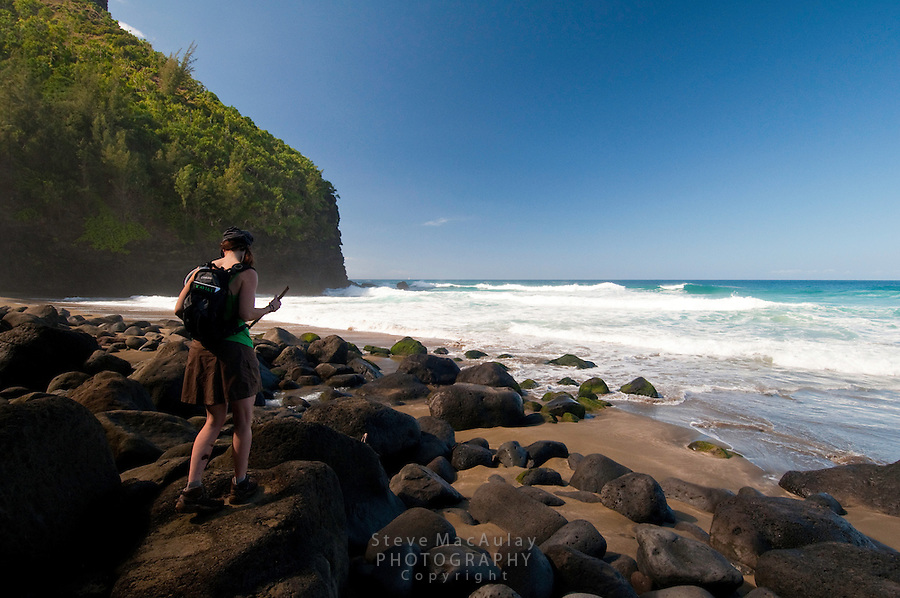 Female hiker, standing on boulders and enjoying the view at Hanakapiai Beach, Napali Coast, Kauai, Hawaii