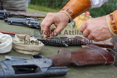 Competitor loads his weapon during the Cowboy Action Shooting European Championship in Dabas, Hungary on August 11, 2012. ATTILA VOLGYI