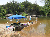 Adults and kids cool off in the War Eagle River at the Gar Hole swimming hole in southeast Benton County. It's a popular spot with people who live in and around Hindsville.