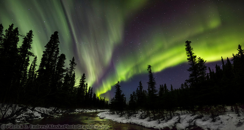 Northern lights reflect in stream in Alaska's interior