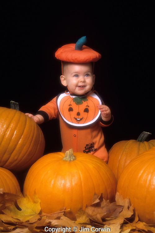 Eight month old baby girl in pumpkin outfit standing with pumpkins with fall leaves indoors