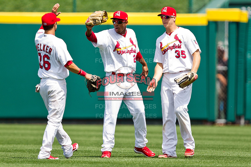 Oscar Taveras (25) of the Springfield Cardinals celebrates with Adam Melker (26) and Kyle Conley (35) during a game against the Arkansas Travelers at Hammons Field on May 8, 2012 in Springfield, Missouri. (David Welker/ Four Seam Images)