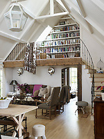 Rustic and industrial make a happy combination with renovated 1930s beams defining the living room and steel shelves for the bookcase