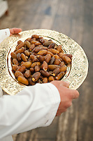 Detail of a platter of fresh dates being carried by a waiter