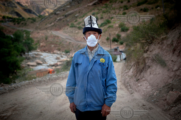 Temiraly Sarbashov, 76, stands at the entrance of the Dump No.3 where he works checking trucks that travel between Dump No.3 and Dump No.6. Workers make about 20,000 Somoni (GBP 2,650) in 2 weeks. Due to the pollution they ingest while working, staff work two weeks on and two weeks off....