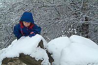 Three year old girl climbing on snowy rocks, Selonnet, French Alps, France.