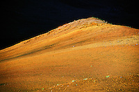 Natural light late in the day cast a warm glow on a cinder cone in the crater of HALEAKALA NATIONAL PARK on Maui in Hawaii