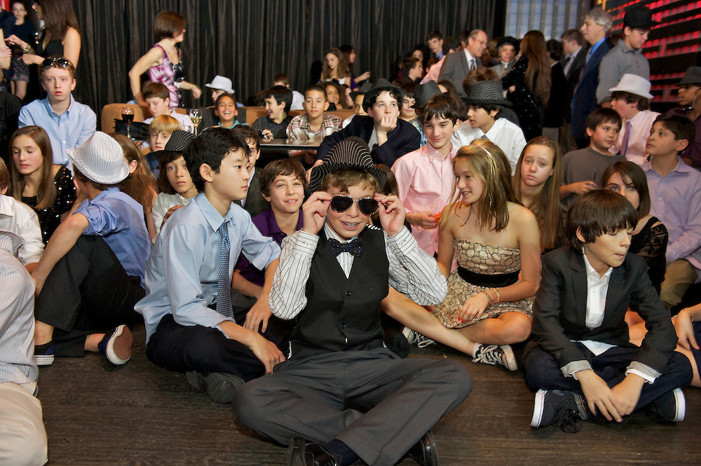 The Bar Mitzvah boy sitting on the dance floor with the kids watching the video montage.