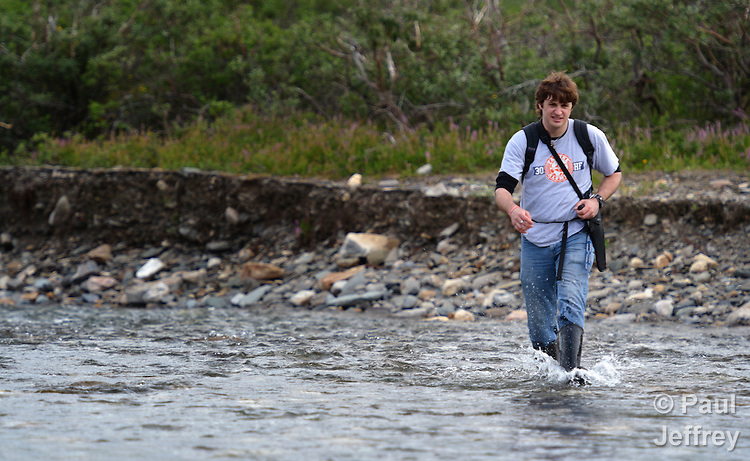 Chris Steppe, a US2 missionary of the United Methodist Church, hikes across a river in the middle of the tundra near Nome, Alaska. Steppe is appointed to the Nome Community Center, where he coordinates programs for youth and elders. The Center is supported by United Methodist Women. Steppe is carrying a pistol because of the danger of encountering grizzly bears..