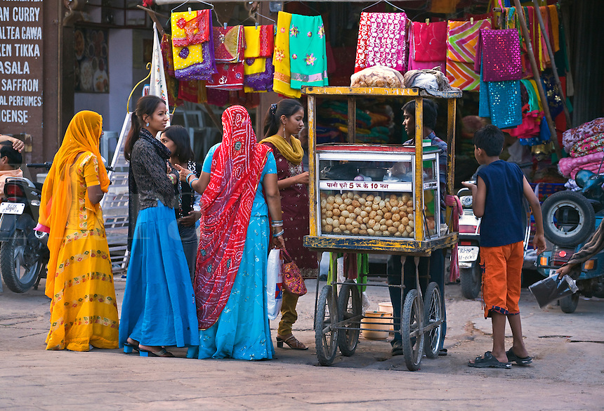 Young girls buy a snack at a food stall in SARDAR  MARKET CIRDIKOT in JOHDPUR known as the BLUE CITY - RAJASTHAN, INDIA
