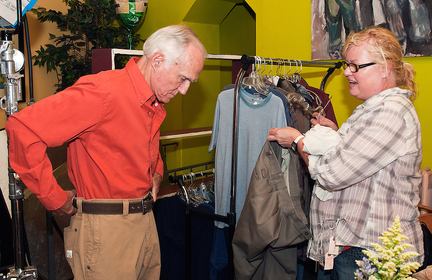Costume designer Katie Maher assists actor Bill McHugh with a change of costume.