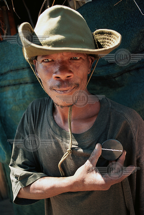 "A Bushman whose badge reads ""Iwant2gohome.org"" prepares to return to his ancestral land in the Central Kalahari Game Reserve after winning the court case against the Botswana government who illegally evicted them in 2002."