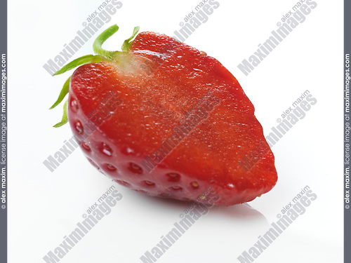 Closeup of red organic homegrown ripe strawberry sliced in half isolated on white background