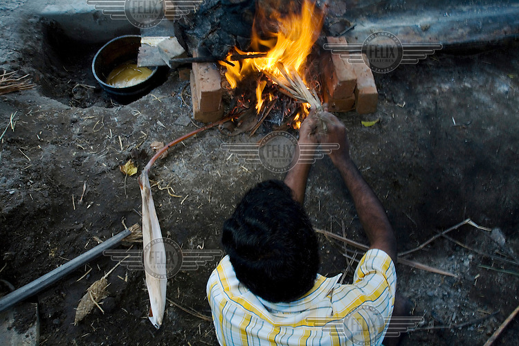 A worker tends the fire that will melt the wax for casting in the pit in the S. Devasenapathy Sthapathy and Sons bronze casting workshop. The current Sthapathy generation is the twenty-third generation of bronze casters. Their method using the lost-wax process remains unchanged to this day.