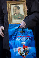 Moscow, Russia, 07/11/2010..A demonstrator carries a portrait of Stalin and a Moscow duty free bag as members and supporters of the Russian Communist Party demonstrate to celebrate the 83rd anniversary of the October 1917 Bolshevik revolution. Russia no longer officially celebrates the anniversary of the 1917 Revolution that brought Vladimir Lenin to power and established communist rule in Russia and the Soviet Union over seven decades.