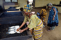 Women preparing fish for smoking in ovens