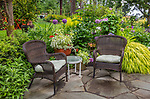 Vashon-Maury Island, WA Summer outdoor seating area with wicker chairs, colorful pots and perennial garden.