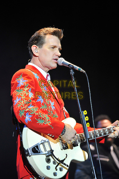 Chris Isaak .performing live at the Hammersmith Apollo, London, England. .9th October 2012.on stage in concert gig performance performing music half length guitar red embroidered suit blue green singing side profile .CAP/MAR.© Martin Harris/Capital Pictures.