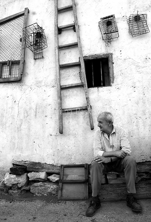 Fifty-seven-year-old Strahil Georgiev rests against the wall of his village home after dining at an upscale restaurant on Aug. 27, 2005. Georgiev is a retired gypsum mineworker in Bulgaria and enjoys a better than average pension.