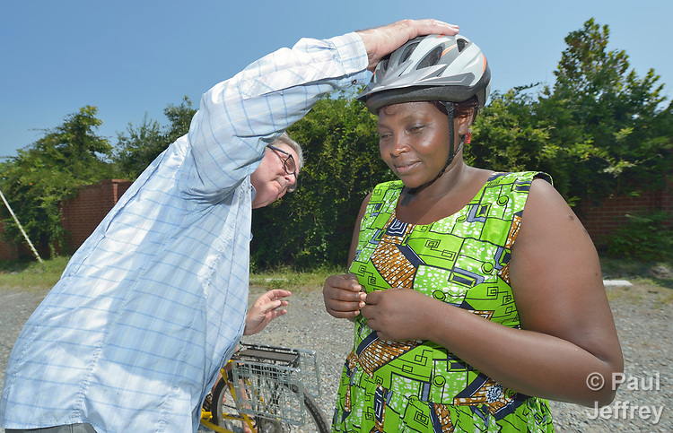 Evanis Gatunzi, a refugee from Rwanda, gets her helmet adjusted before riding a bike for the first time in Durham, North Carolina, on July 22, 2017. She&rsquo;s helped by Greg Garneau, a volunteer who coordinates the refugee bike program for the Durham Bicycle Co-op.<br /> <br /> Gatunzi was resettled in Durham by Church World Service, which resettles refugees in North Carolina and throughout the United States.<br /> <br /> Photo by Paul Jeffrey for Church World Service.