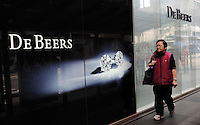 A woman walks pass a De Beers jewellery shop in Central District, Hong Kong. De Beers and the various companies within the De Beers Family of Companies are in the diamond, diamond mining, diamond trading and industrial diamond manufacturing sectors. It is by far the largest company in all these categories..
