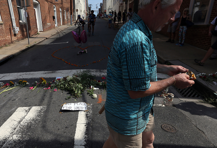 A man walks past a make-shift memorial of flowers on 4th Street SE Sunday where a woman was killed and several other injured after a Unite the Right rally in Charlottesville, Va. Photo/Andrew Shurtleff