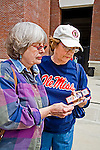 Two mature women compare their tickets for seats at baseball game outside of stadium at University of Mississippi in Oxford, Mississippi