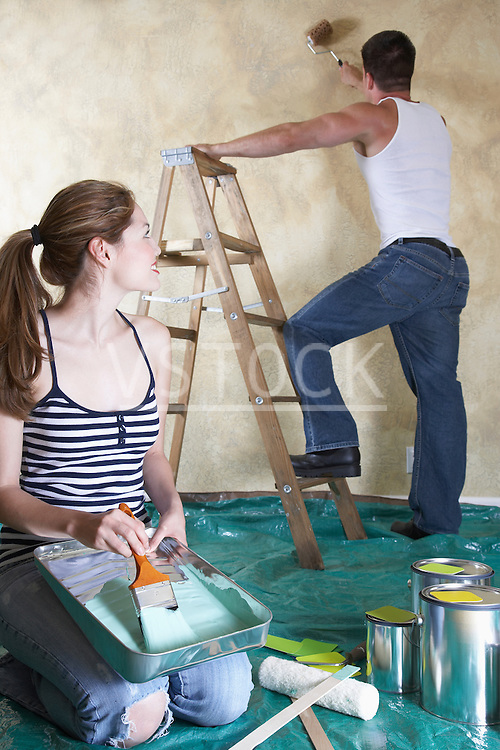 Young woman holding paint tray, man painting wall with roller in background