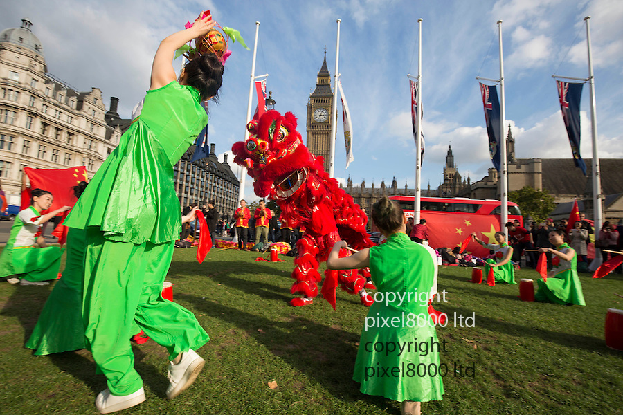 Pic shows: Protests by 'Free Tibet' supports were disrupted by entertainment in the shape of dragon dancers<br /> <br /> Taking place opposite Houses of Parliament in London today 20.10.15<br /> <br /> <br /> <br /> <br /> Pic by Gavin Rodgers/Pixel 8000 Ltd