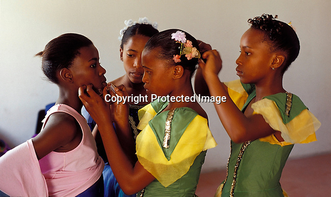 """ACDANCE03144.Arts & Crafts. Dance. Young ballet dancers from the townships of Guguletu and Khayelitsha. Part of the """"Dance for All"""" outreach programme run by the Cape Town  City Ballet. Girls in costumes, tutus. Girls preparing each others make - up and hair. .©Per-Anders Pettersson/iAfrika Photos"""