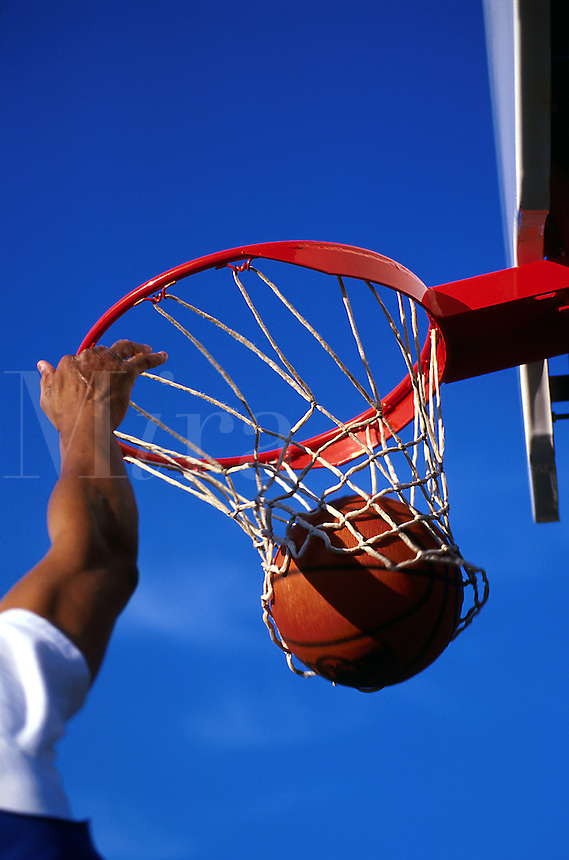 A ball swishes through the hoop and decends through the net as the hand of a male player lingers nearby.