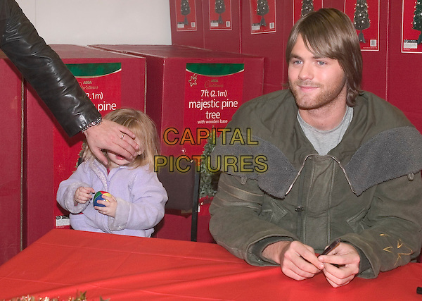 BRIAN McFADDEN (WITH BABY MOLLY McFADDEN)<br /> at record signing, ASDA store, Trafford Park Manchester, 1st December 2004.<br /> half length bryan daughter eyes covered hiding child family<br /> Ref: AT<br /> www.capitalpictures.com<br /> sales@capitalpictures.com<br /> &copy;Alan Towse/Capital Pictures