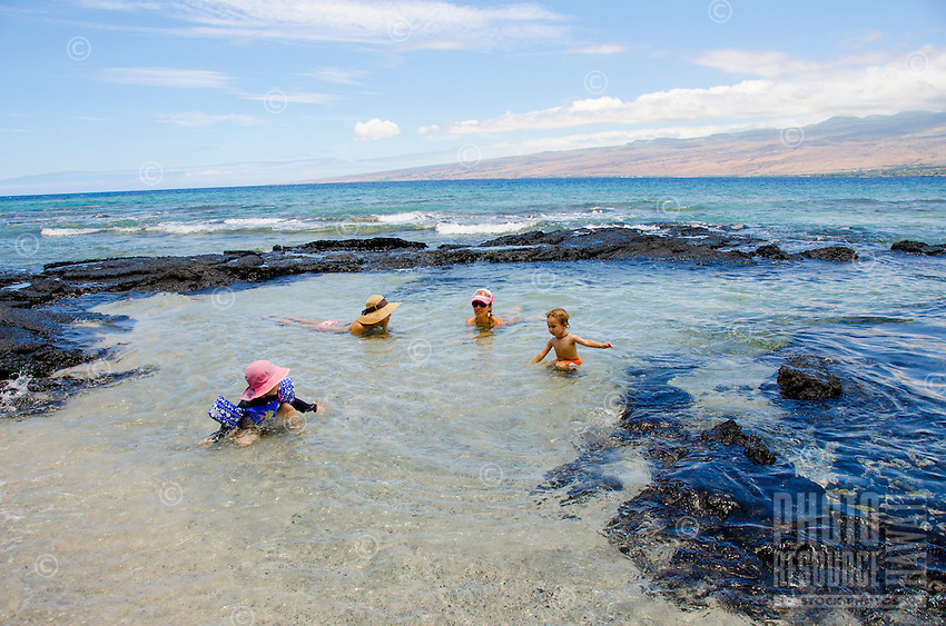 A young girl with arm floaties plays with a young boy while their mothers look on in a tide pool at Puako, South Kohala, Big Island.