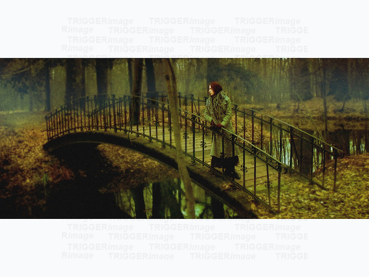 A woman ina  coat, standing on a little bridge above a river in a wood.