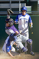 Air Force Falcons designated hitter Griffin Jax (22) slides safely home upending Washington catcher Parker Guinn (26) during the NCAA season opening baseball game against the Washington Huskies on February 14, 2014 at Bobcat Ballpark in San Marcos, Texas. Air Force defeated Washington 14-9. (Andrew Woolley/Four Seam Images)