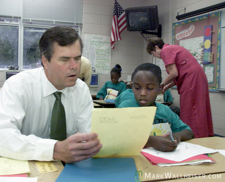 Florida Governor Jeb Bush helps 8year old Darryl Sanders who had been drawing and coloring the country of Argentina for his spanish class at Ruediger Elementary School in Tallahassee, Florida this morning September 6,2000.  Bush was at the school to present a check to them for raising their school grade from a C to and A.  While there, he read Pollita Chiquita or the spanish version of Chicken Little to Sanders' class.
