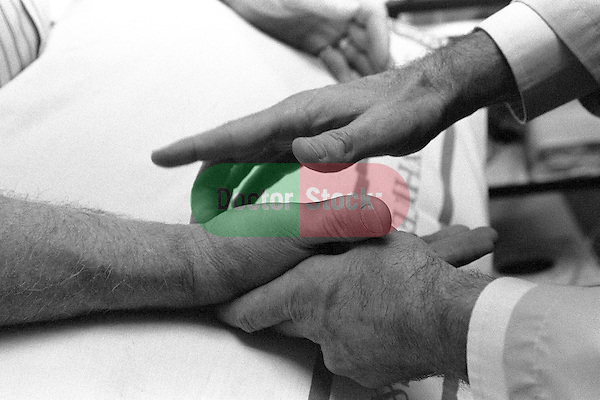 Close-up of doctor's hands holding patient's hand; tapping patient's wrist to test nerve conduction, Carpal Tunnel Syndrome