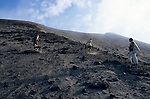 Tourist with two local guides climbing the sloped terrain of Yasur Volcano, Tanna Island, Vanuatu.
