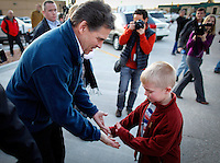 Gov. Rick Perry high-fives seven-year-old Eric Torneten of Harlan, Iowa while campaigning in Carroll, Iowa on Monday, January 2, 2012.  (Christopher Gannon/GannonVisuals.com/MCT)