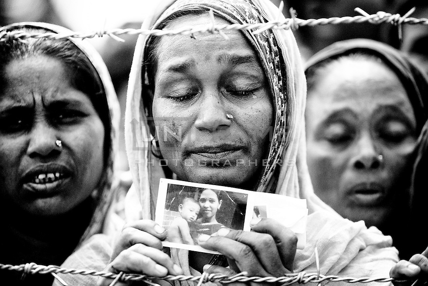 A woman shows a portrait of her missing daughter, believed trapped in the rubble following the collapse of an an eight-storey building Rana Plaza in Sava, near Dhaka, Bangladesh