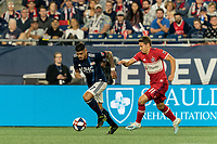 FOXBOROUGH, MA - AUGUST 24: Gustavo Bao #7 of New England Revolution dribbles as Przemyslaw Frankowski #11 of Chicago Fire defends during a game between Chicago Fire and New England Revolution at Gillette Stadium on August 24, 2019 in Foxborough, Massachusetts.
