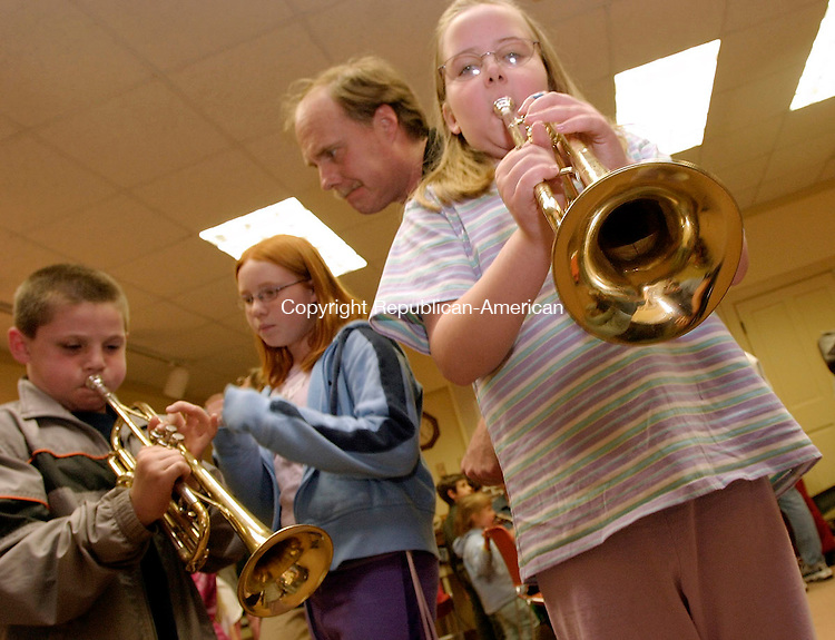 HARWINTON, CT - 25 MARCH 2005 -  052505JS06--Shannon Lusk, 9, of Harwinton, right, tries her hand on a trumpet as Nick Hull, 9,  and his sister Rebecca, 10 get help from their father Doug during the Hartford Symphony Orchestra's instrument zoo held Wednesday at the Harwinton Public Library. Students were allowed to try their hand on different instruments. The instrumnet zoo is part of the Musical Pathways education program of the Hartford Symphony Orchestra and sponsored by the Target Corporation. --Shannon Lusk; Hartford Symphony Orchestra; Harwinton; Target, Nick Hull, Rebecca Hull, Doug Hull tare CQ