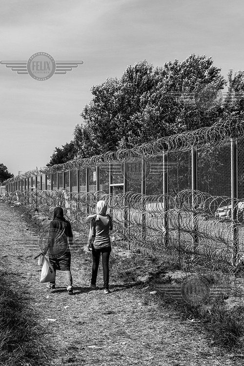 Refugee woman walk past the razor wire at the border between Horgos, Serbia and Roszke, Hungary which remains closed after Hungarian authorities closed the crossing.