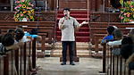 Pastor Edwin Abag speaks to people in the sanctuary of Knox United Methodist Church in Manila, Philippines. Once a week the church opens up to poor residents of the neighborhood, offering food, showers, fellowship, a meal, worship, and an educational opportunity for children.